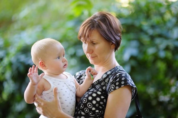 Mooie vrouw van middelbare leeftijd en haar schattige kleine kleinzoon in het zomer park Premium Foto