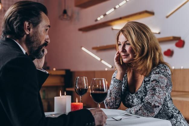 Mooie vrouw van middelbare leeftijd kijkt naar een man met een liefdevolle uitstraling. Premium Foto