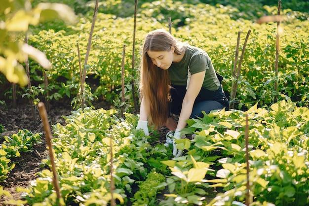 Mooie vrouw werkt in een tuin in de buurt van het huis Gratis Foto