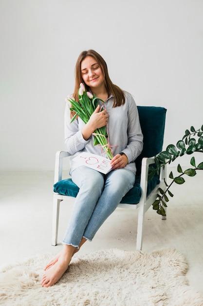 Mooie vrouw zitten met tulpen en wenskaart Gratis Foto