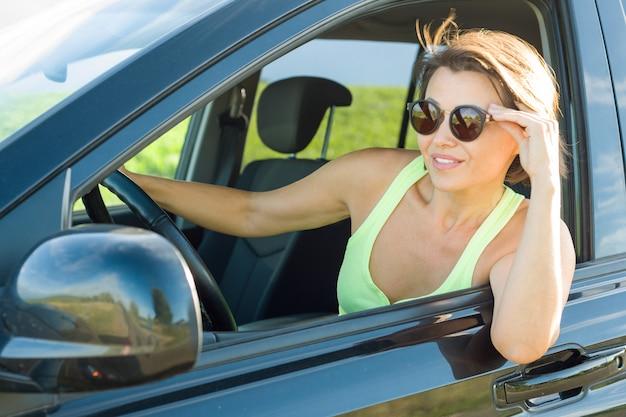Mooie vrouwelijke bestuurder die terwijl het drijven van zijn auto glimlacht Premium Foto