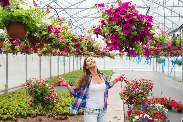 Mooie vrouwelijke bloemist die ingemaakte bloemplanten in kas houdt die zich gelukkig en positief voelen Gratis Foto