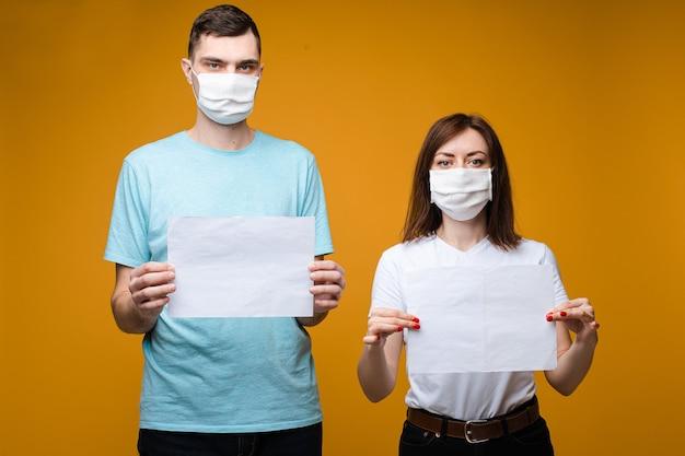 Mooie vrouwelijke en knappe man staat in de buurt van elkaar in een witte en blauwe t-shirts en witte medische maskers en houdt vellen papier Gratis Foto