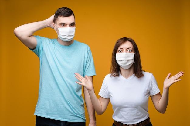 Mooie vrouwelijke en knappe man staat in de buurt van elkaar in een witte en blauwe t-shirts en witte medische maskers en wil gezond zijn Gratis Foto
