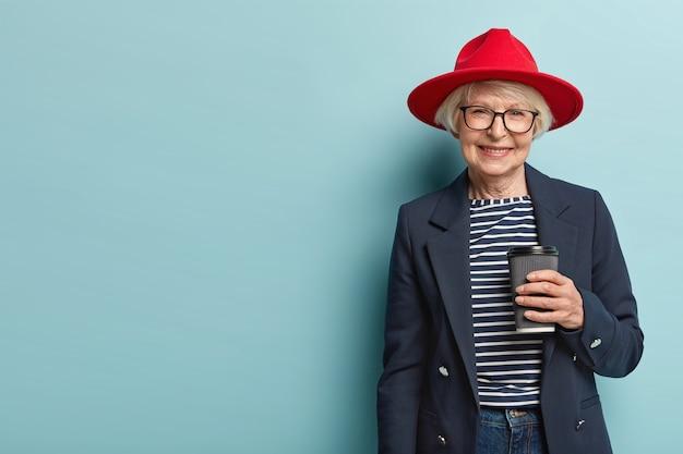 Mooie vrouwelijke gepensioneerde m / v heeft ontmoeting met collega, bespreekt iets tijdens koffiepauze, houdt papieren kopje cappuccino, draagt stijlvolle outfit, geïsoleerd op blauwe muur, kopie ruimte aan de linkerkant Gratis Foto