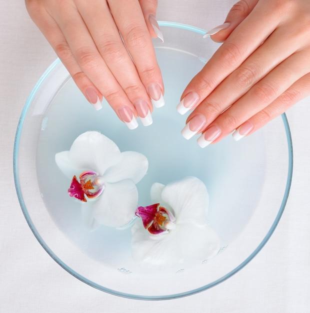 Mooie vrouwelijke handen met franse manicure krijgen spa-procedure krijgen Gratis Foto