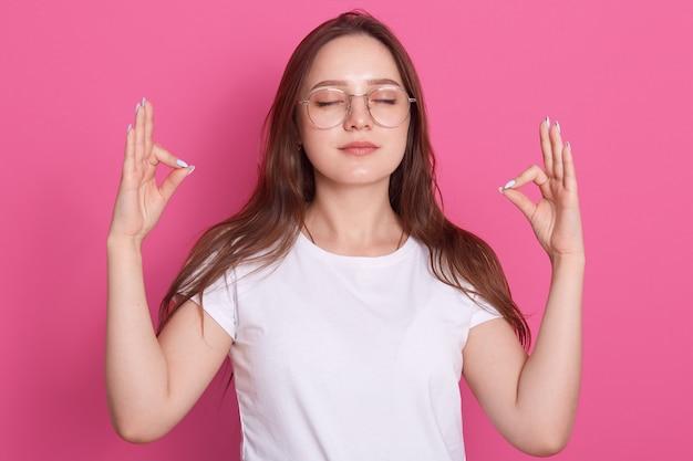 Mooie vrouwelijke jurken wit casual t-shirt mediteren met gesloten ogen, ontspannend lichaam en heldere geest Gratis Foto