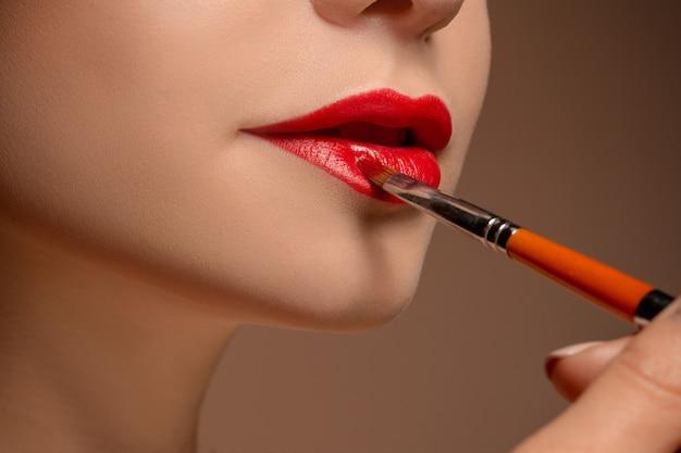 Mooie vrouwelijke lippen met make-up en borstel Gratis Foto