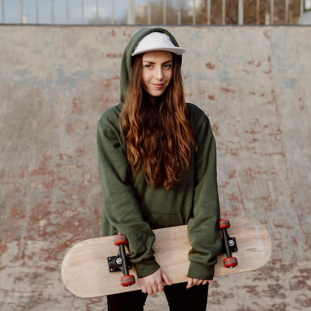 Mooie vrouwelijke skater die haar skateboard vooraanzicht houdt Premium Foto