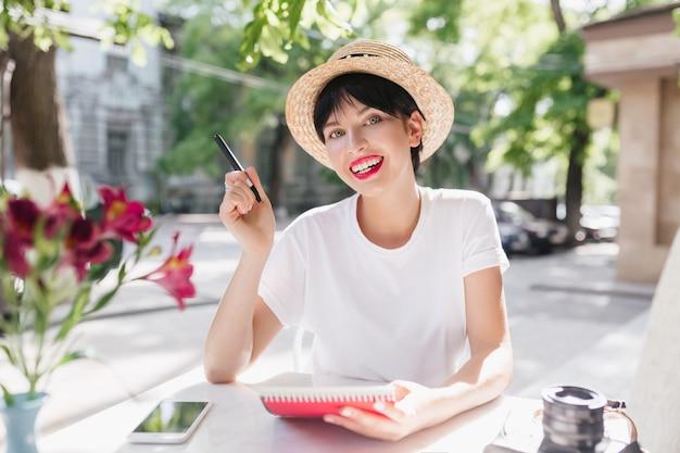 Mooie vrouwelijke student die in tuin met notitieboekje en pen koelen die bloemsmaak geniet Gratis Foto
