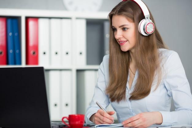 Mooie vrouwelijke student met koptelefoon luisteren naar muziek en leren. houd het handvat in zijn hand en kijkend naar laptop monitor Premium Foto