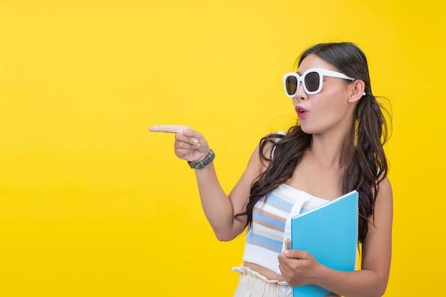 Mooie vrouwelijke studenten houden notitieboekjes en pennen Gratis Foto