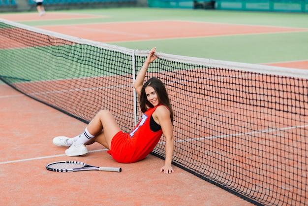 Mooie vrouwelijke tennisspeelster op tennisbaan in rode jurk. Premium Foto