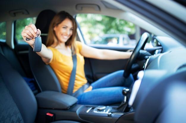 Mooie vrouwelijke vrouwenbestuurder die in haar voertuig zitten en autosleutels klaar voor een rit houden Gratis Foto