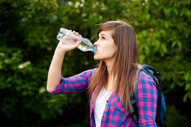 Mooie vrouwelijke wandelaar drinkwater in het bos Gratis Foto
