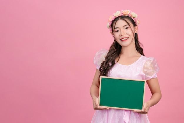 Mooie vrouwen gekleed in roze prinses jurken houden een groen bord op een roze. Gratis Foto