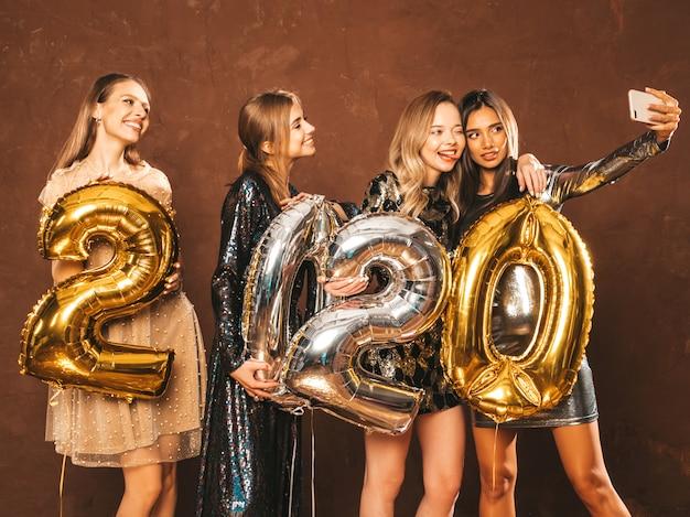 Mooie vrouwen nieuwjaar vieren. gelukkige prachtige meisjes in stijlvolle sexy feestjurken met gouden en zilveren 2020-ballonnen, plezier hebben op oudejaarsfeest. selfie of video maken voor instagram Gratis Foto