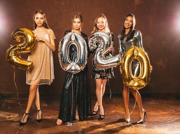 Mooie vrouwen nieuwjaar vieren. gelukkige prachtige meisjes in stijlvolle sexy feestjurken met gouden en zilveren 2020-ballonnen, plezier op oudejaarsfeest. vakantieviering. charmante modellen Gratis Foto