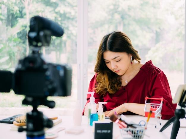 Mooie vrouwen van vloger gebruiken internet online om haar cosmeticamerk te beoordelen Premium Foto