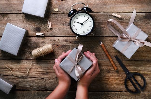 Mooie vrouwenhanden die giftdoos op houten houden. zwarte wekker, pen, schaar. Premium Foto