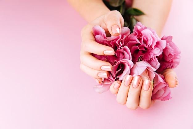 Mooie vrouwenhanden met verse eustoma. spa en manicure concept. vrouwelijke handen met roze manicure. zachte huidverzorging concept. schoonheid nagels. over beige achtergrond Premium Foto