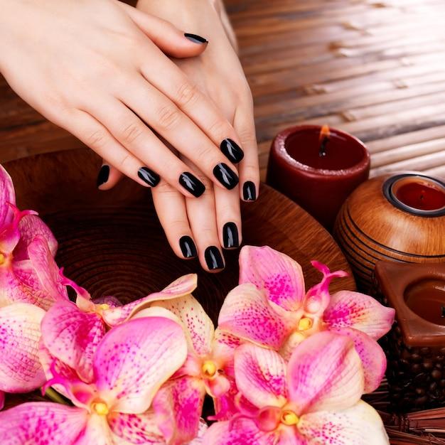 Mooie vrouwenhanden met zwarte manicure na kuuroordprocedures - kuuroordbehandelingconcept Gratis Foto