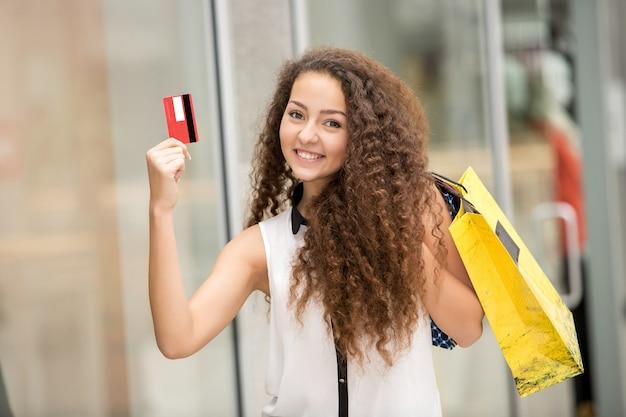 Mooie vrouwenholding het winkelen zakken en het tonen van lege creditcard Gratis Foto