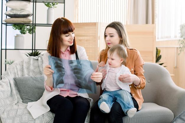 Mooie vrouwenhuisarts die xray beeld tonen aan jonge moeder met vrolijk babymeisje op haar handen Premium Foto