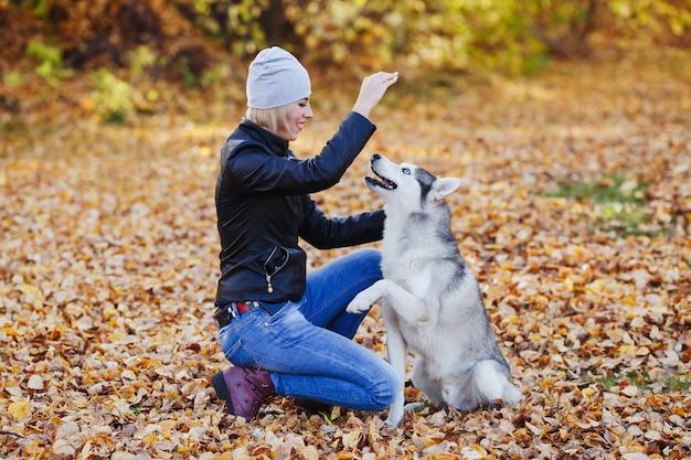 Mooie vrouwenspelen met schor hond in de herfstbos Premium Foto