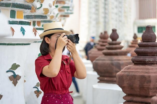 Mooie vrouwentoerist hield camera om de herinneringen te vangen Premium Foto