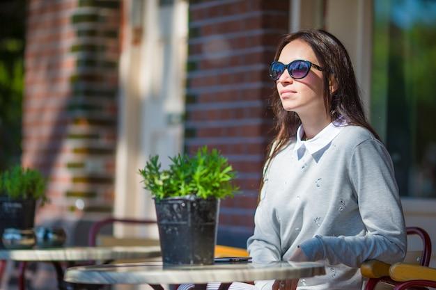 Mooie vrouwenzitting in in openlucht koffie bij europese stad Premium Foto