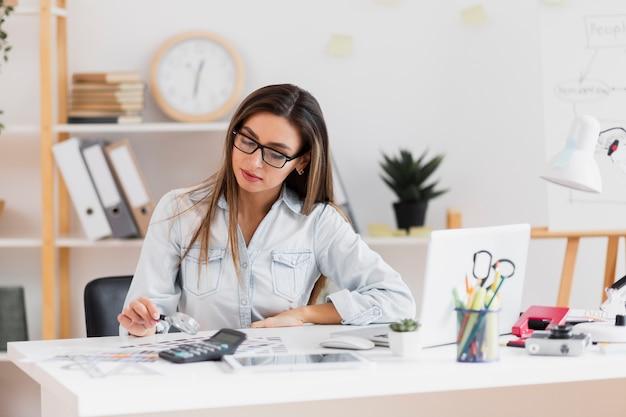 Mooie vrouwenzitting op kantoor en holding een vergrootglas Gratis Foto