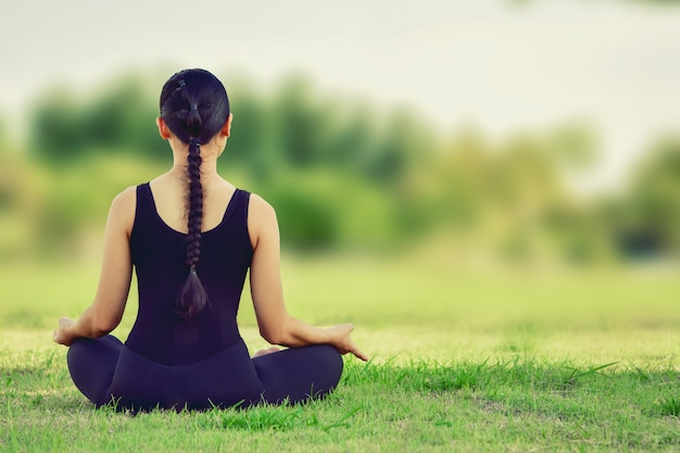 Mooie vrouwenzitting op yogahoudingen voor een uitgebalanceerde oefening van het lichaam. Premium Foto