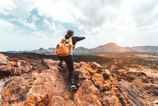 Mooie wandelaarvrouw op de bovenkant van de berg die op de zonsondergangvallei richten. meisje met rugzak alleen reizen in de natuur. Premium Foto