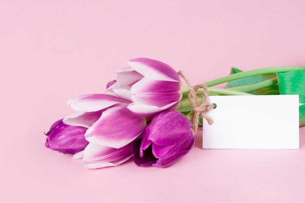 Mooie wenskaart met bloemen van tulpen op roze achtergrond Premium Foto