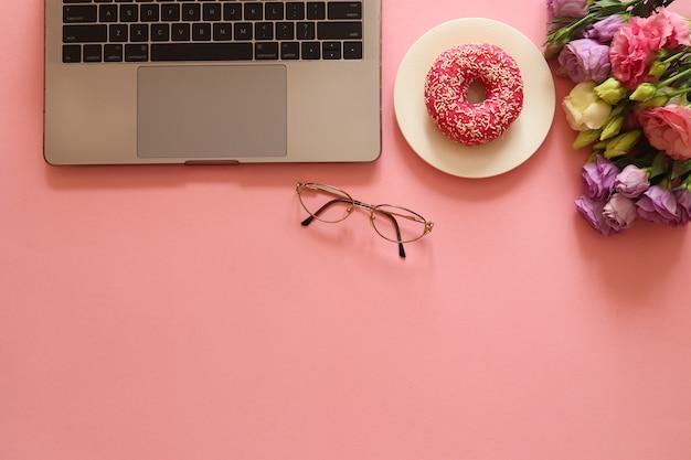 Mooie werkplek met laptop, bril, donut en bloemen Premium Foto