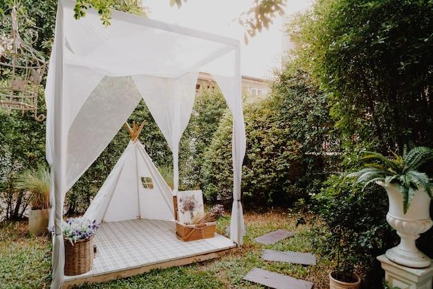Mooie witte tent en kampdecoratie in huistuin Premium Foto