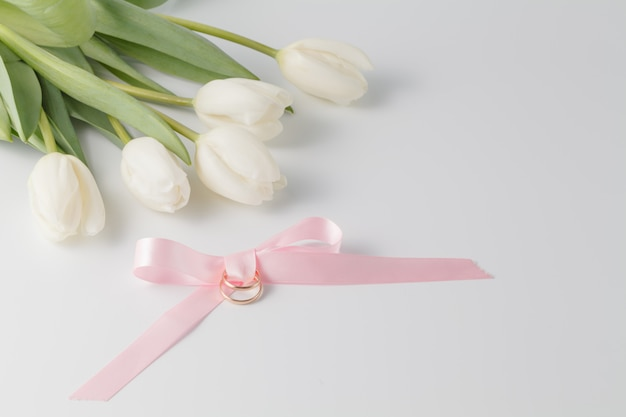 Mooie witte tulpen, roze lint en trouwringen Premium Foto
