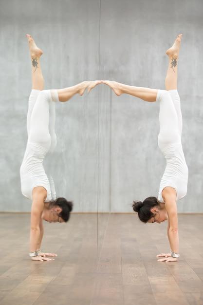 Mooie yoga: vrouw doet handstandhouding Gratis Foto