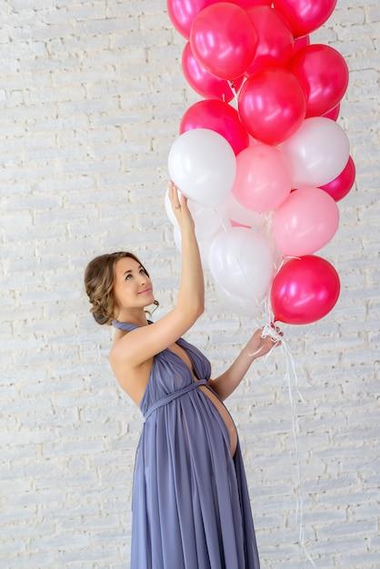 Mooie zachte zwangere vrouw met ballonnen Premium Foto