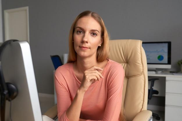 Mooie zakelijke dame zittend in een comfortabele baas-fauteuil in haar kantoor Gratis Foto