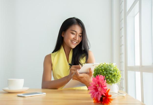 Mooie zakenvrouw draagt een geel shirt zit op kantoor het controleren van documenten om zijn businessplannen gelukkig te controleren Premium Foto