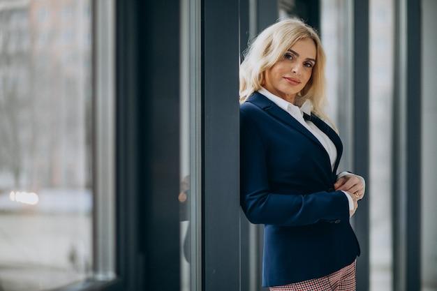 Mooie zakenvrouw op kantoor bij het raam Gratis Foto