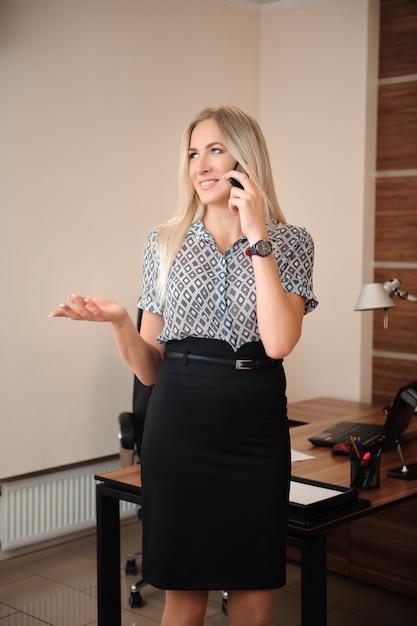 Mooie zakenvrouw praten op mobiele telefoon. het jonge vrouwelijke modelwerk met verkoop in bureau. Premium Foto