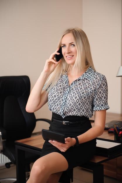 Mooie zakenvrouw praten op mobiele telefoon. het jonge vrouwelijke modelwerk met verkoop in helder bureau. Premium Foto