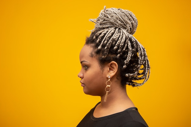 Mooie zij jonge afrikaanse amerikaanse vrouw met ontzettingshaar op geel Premium Foto
