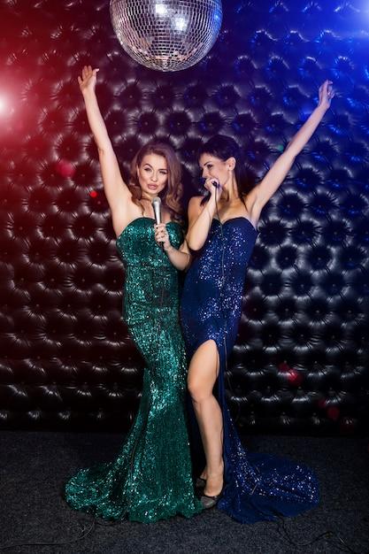 Mooie zingende meisjes met microfoon karaoke lied op het podium Premium Foto
