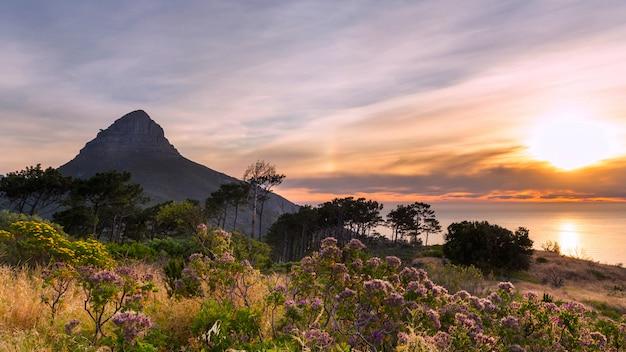 Mooie zonsondergang over de oceaan en de bergmening van lion's head van signaalheuvel in cape town Premium Foto
