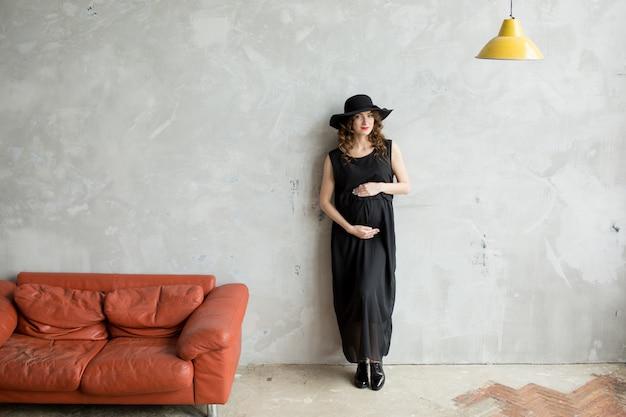 Mooie zwangere vrouw in zwarte jurk en hoed door muur Premium Foto
