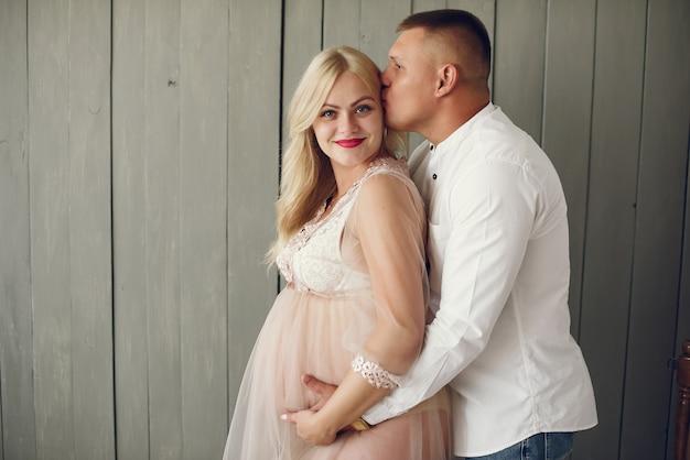 Mooie zwangere vrouw met haar echtgenoot in een studio Gratis Foto
